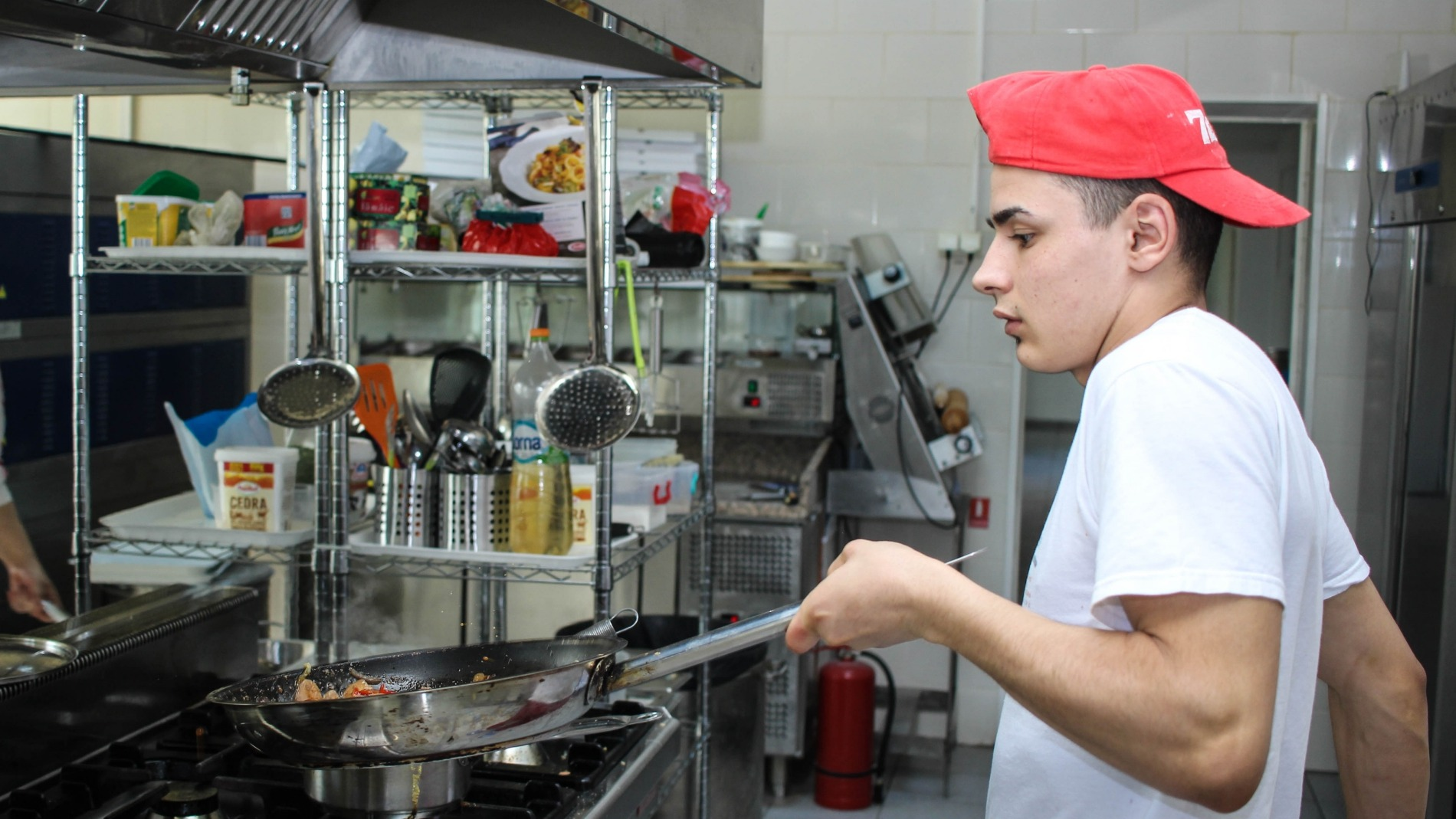 Young person cooking in a professional kitchen